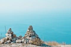 2 пирамидки камней против голубого моря Стоковое Изображение RF