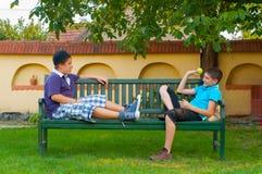 2 подростка сидя на стенде и бросать Стоковые Изображения RF