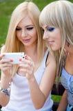 2 подруги используя smartphone Стоковая Фотография RF