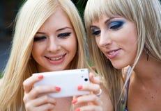 2 подруги используя smartphone Стоковые Фотографии RF