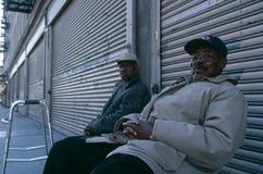 2 пожилых люд сидели вне закрытых магазинов, Манхаттана, нью-йорк, США Стоковое Изображение RF