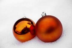 2 померанцовых Baubles в снежке Стоковое Изображение