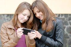 2 предназначенных для подростков девушки смотря на ПК таблетки Стоковые Фото