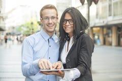 2 предпринимателя на улице с компьютером таблетки Стоковые Изображения