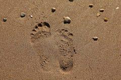 2 различных следа ноги на песке Стоковые Изображения