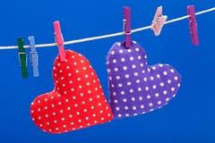 2 сердца вися на веревке для белья с зажимками для белья Стоковые Изображения RF