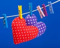 2 сердца вися на веревке для белья с зажимками для белья Стоковые Фотографии RF