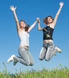 2 сестры в джинсыах скача outdoors Стоковые Изображения RF