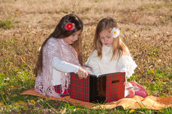 2 сестры девушок прочитали книгу на траве Стоковое фото RF