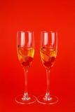 2 стекла с шампанским и вишнями на красном цвете Стоковое фото RF