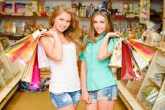 2 счастливых молодой женщины с хозяйственными сумками Стоковые Фото