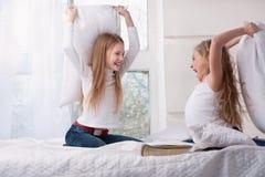 2 девушки сидя драка подушки в кровати. Стоковые Изображения RF