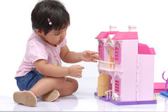 2-3 years old baby girl. Observing doll house Royalty Free Stock Photography
