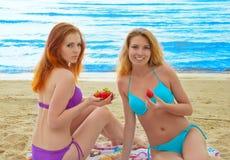 2 красивых молодой женщины есть клубнику. Стоковая Фотография RF