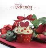 与玫瑰和装饰的美丽的红色心脏华伦泰题材杯形蛋糕2月 免版税库存照片