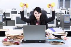 妇女工作和锻炼在办公室2 库存照片
