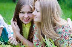野餐的时刻:说谎在草愉快的微笑的2个美丽的女朋友少妇有乐趣&一台看的照相机 库存图片