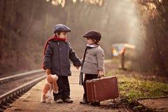2 мальчика на железнодорожном вокзале, ждать поезд Стоковые Фотографии RF