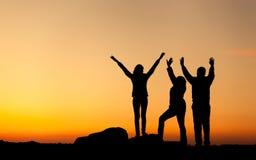 Силуэт счастливой семьи с оружиями поднял вверх против красивого неба за валами 2 захода солнца лета сосенки стоящими Стоковое Изображение