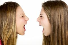 2 сердитых белокурых девушки кричащей на изолированном одине другого Стоковая Фотография RF