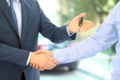 Продавец автомобилей вручая над ключами для нового автомобиля к молодому бизнесмену люди 2 рукопожатия дела Фокус на ключе Стоковые Фото