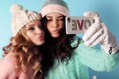 2 красивых девушки в теплых уютных одеждах имея потеху в студии Стоковая Фотография RF