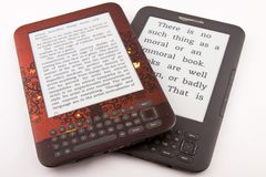 2 Amazon Kindle E-Readers (Different Font Sizes). 2 Amazon Kindle ereaders, both displaying the same book but with different font sizes.  This image clearly Stock Photos