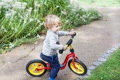 2 années d'équitation d'enfant en bas âge sur son premier vélo Image stock