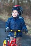 2 années d'équitation d'enfant en bas âge sur son premier vélo Photos stock