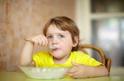 2 anos de criança ele mesmo comem da placa Foto de Stock