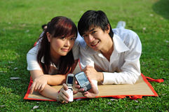 2 asiatiska par parkerar telefonbarn Royaltyfri Bild