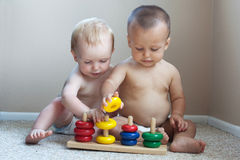 2 babies playing with toys inside Royalty Free Stock Photography