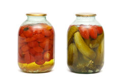 2 banks with pickles and tomatoes. On a white background Royalty Free Stock Photo