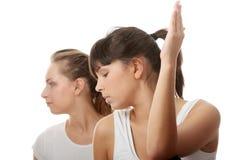 2 beaux jeunes womans faisant l'exercice de yoga Image stock