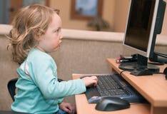 2 behandla som ett barn datorskrivbordsflickan little som använder Arkivbild