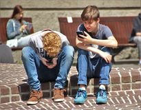 2 Boy Sitting on Brown Floor While Using Their Smartphone Near Woman Siiting on Bench Using Smartphone during Daytime Stock Images