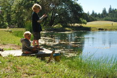 2 Boys Fishing. Two blond boys fishing on pond royalty free stock photography