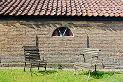 2 chairs in front of brick wall. 2 old chairs in front of an old wall with window and roof royalty free stock image
