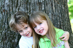 2 children discovering nature. 2 children sitting by a large tree Royalty Free Stock Photography