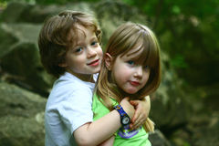 2 children discovering nature. 2 children sitting by a large tree Royalty Free Stock Photos