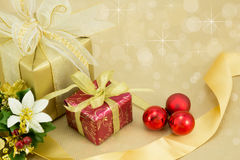 2 Christmas Presents with red baubles.. Beautifully wrapped presents with red baubles and gold sparkle background Royalty Free Stock Photo