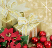 2 Christmas Presents with ribbon and bows . Beautifully wrapped presents with gold sparkle background Royalty Free Stock Photo