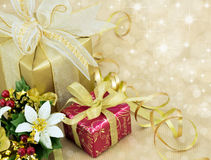 2 Christmas Presents with ribbon and bows . Beautifully wrapped presents with gold sparkle background Royalty Free Stock Image