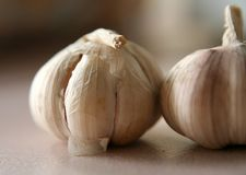 2 cloves of garlic. Short-focused image of 2 cloves garlic on top of ceramic tile Stock Photo