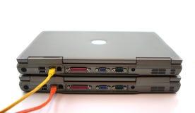 2 ordenadores portátiles con los cables de la red foto de archivo