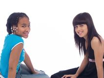 2 cute girls posing. 2 cute girls with different ethnic backgrounds Royalty Free Stock Images