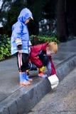 2 fartygpojkar som leker regn, toy barn Arkivfoto