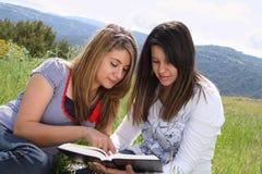 2 flickor som tillsammans läser royaltyfria foton