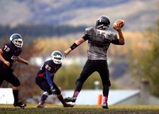 2 Football Player Running After Person Holding Football during Daytime in Shallow Focus Photography Royalty Free Stock Photography