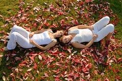 2 Freundinnen, die sich zwischen Herbstblättern hinlegen Stockbilder